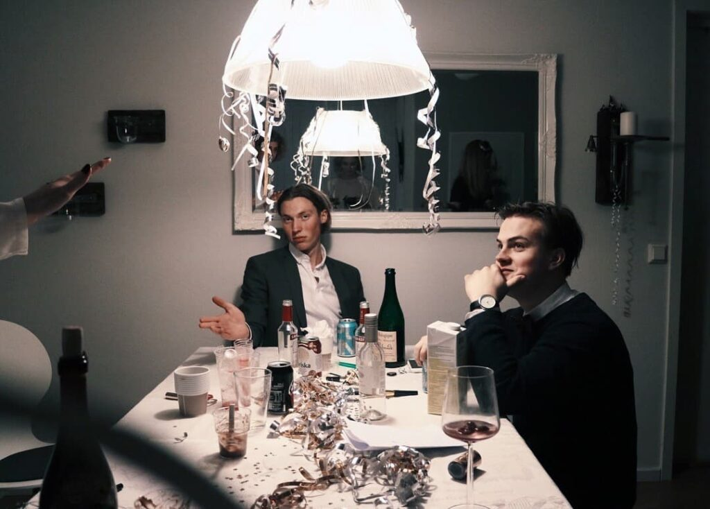 image from a party, two men sitting at a table, one looking in to the camera and the other one looking to the left