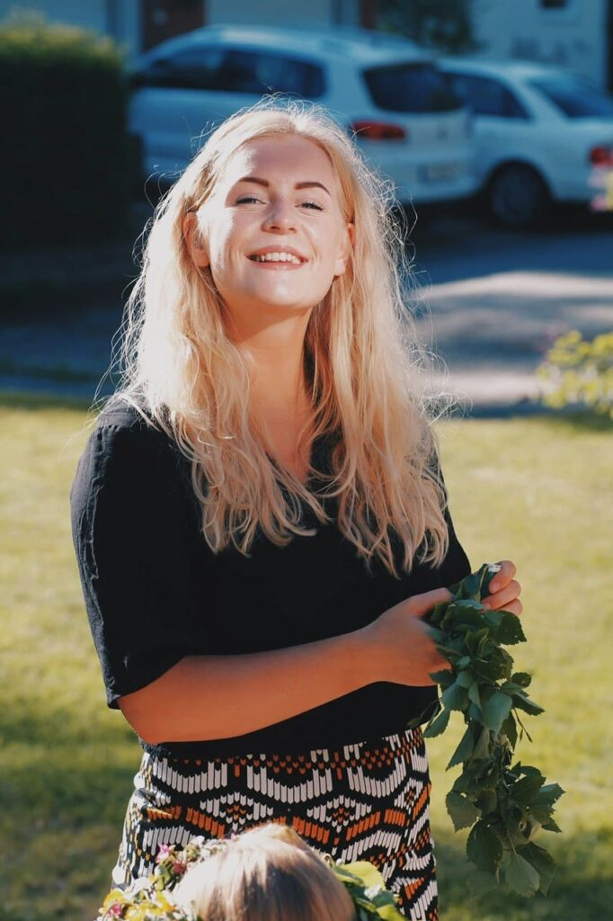 happy blond woman looking in to the camera while creating a flower crown