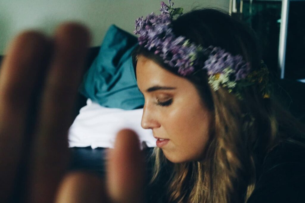 woman wearing flower crown, viewing left profile, image cropped from sholders upp. brown hair