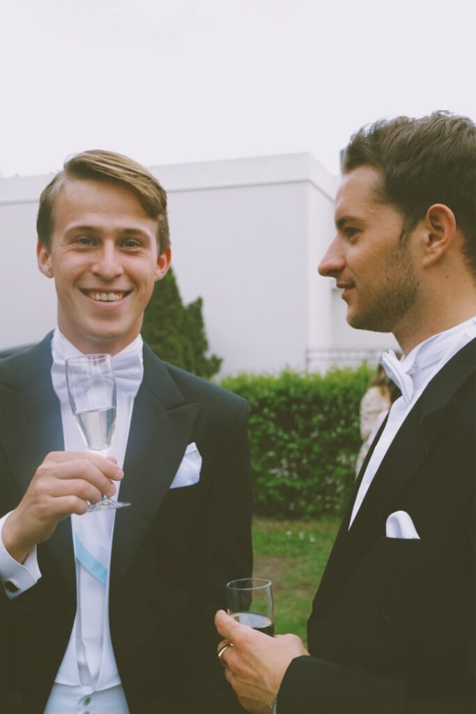 men dressed in suits, one looking in to the camera while holding a class of champagne the other looking to the left.